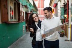 英俊的看地图的男人和逗人喜爱的妇女 库存图片