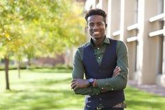 英俊的确信的年轻黑人学生人在colege阵营微笑 图库摄影