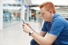 英俊的红头发人人一张斜向一边的画象有时髦的发型的在蓝色衬衣穿戴了有休息在聪明的商城对负 免版税库存图片