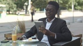 英俊的美国黑人的人在外部咖啡馆时使用一种片剂,当坐 免版税库存照片