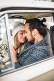 英俊的行家男人和秀丽妇女互相亲吻坐在减速火箭的汽车的 Valintine ` s天概念 垂直 库存图片