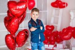 英俊的行家青少年摆在与红色心脏baloon在演播室 去在演播室的日期的黄色衬衣的年轻人 库存照片
