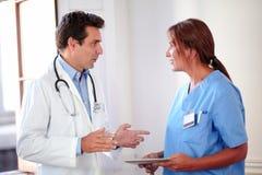 英俊的西班牙医生谈话与夫人护士 库存照片