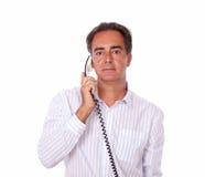 英俊的资深男性交谈在电话 免版税图库摄影