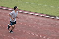 英俊的跑在跑马场的运动员亚裔人在体育场内有拷贝空间背景 健康活跃生活方式概念 免版税库存照片