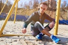 英俊的运动人坐海滩足球的沙子领域 免版税库存照片