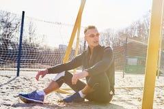 英俊的运动人坐海滩足球的沙子领域 库存图片