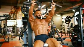 英俊的运动员在健身房中心行使 爱好健美者人坚硬训练干涉在训练机器 股票录像