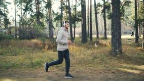 英俊的运动员在公园跑步并且享受在耳机的音乐及时时间 现代技术,青年文化 影视素材