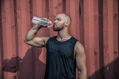 英俊的运动员是从瓶的饮用水充满享受 他站立反对都市背景 他闭上了他的眼睛与 免版税库存图片