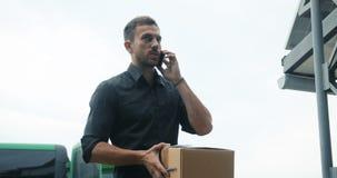 英俊的送货人传讯者手机电话室外城市街道,年轻可爱的商人偶然深灰衬衣 股票视频