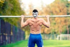 英俊的适合白种人人,赤裸上身,做引体向上在公园,户外 健身训练在一个夏天晴天 免版税库存照片