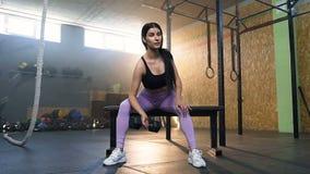英俊的适合的使用哑铃的妇女训练手在健身房 股票视频