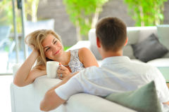 英俊的长发年轻白肤金发的妇女坐长沙发用一只手和拿着一个杯子扶植了她的头在的可口茶 免版税库存图片
