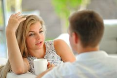 英俊的长发年轻白肤金发的妇女坐长沙发用一只手和拿着一个杯子扶植了她的头在的可口茶 免版税库存照片