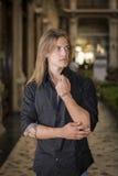 英俊的长的户内头发年轻人在典雅的画廊 免版税图库摄影