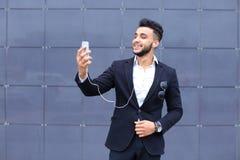 英俊的阿拉伯人在商业中心采取selfie巧妙的电话 库存图片