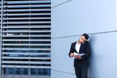 英俊的阿拉伯人在手机在商业中心谈话 图库摄影