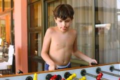 英俊的青春期前的男孩戏剧桌足球在海滩胜地旅馆rec里 库存图片