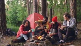 英俊的非裔美国人的人倾吐从热水瓶的热的饮料入坐在火附近的玻璃和杯子在阵营 影视素材
