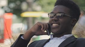 英俊的非裔美国人的人在他的手机笑并且谈话 库存图片