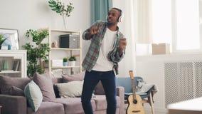 英俊的非裔美国人的人是跳舞和唱平展听到音乐通过在光的耳机 人佩带 股票录像