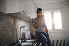 英俊的非裔美国人的人饮用的咖啡在厨房里 免版税图库摄影