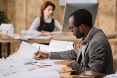 英俊的非裔美国人的建筑师图画大厦计划,当他的同事工作时 免版税图库摄影