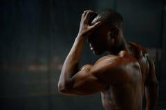 英俊的非裔美国人的男性身体建造者特写镜头画象与显示赤裸的躯干的摆在和在黑色干涉 免版税库存图片
