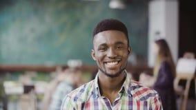 英俊的非洲人在繁忙的现代办公室 看照相机和微笑的年轻成功的男性画象  免版税库存图片