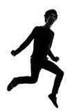 英俊的非洲年轻人跳的叫喊的剪影 库存照片