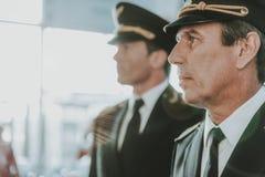 英俊的飞行员和年轻副驾驶身分在机场 免版税库存图片