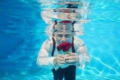 英俊的给一朵红色玫瑰花的新郎水下的潜水 免版税图库摄影