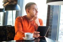 英俊的年轻人与片剂,认为一起使用,看窗口,当享用在咖啡馆时的咖啡 图库摄影