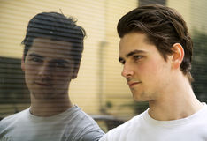 英俊的年轻人和他的反射在商店窗口里 免版税库存图片
