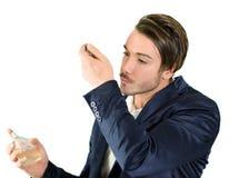 英俊的年轻人嗅到的香水或科隆香水 免版税图库摄影