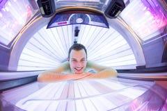 英俊的年轻人在一个现代日光浴室 免版税库存图片