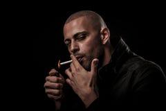 英俊的年轻人在黑暗-摄影中抽香烟  库存照片