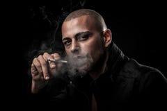 英俊的年轻人在黑暗-摄影中抽香烟  免版税库存照片