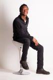 英俊的黑人坐椅子 免版税库存照片