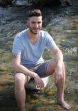 英俊的年轻人坐河岩石 库存图片