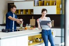 英俊的年轻人开头酒瓶,当他的使用数字式片剂的妻子在厨房时 免版税图库摄影