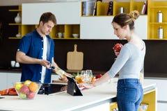 英俊的年轻人开头酒瓶,当他的使用数字式片剂的妻子在厨房时 免版税库存照片