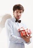 英俊的年轻人当与礼物的丘比特天使 免版税库存图片