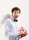 英俊的年轻人当与礼物的丘比特天使 图库摄影
