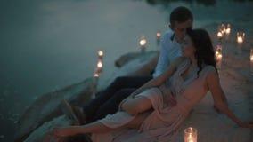 英俊的年轻人拥抱并且亲吻浅粉红色的礼服的迷人的女孩,当说谎在与蜡烛光时的含沙岸 影视素材