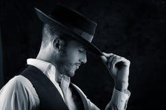 英俊的年轻人有帽子黑色背景 免版税库存图片