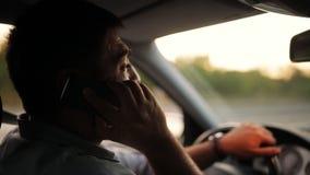 英俊的年轻人谈话在手机,当驾驶他的汽车时 危险,冒失驾驶员恶习 交通安全 影视素材