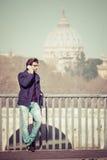 英俊的年轻人谈话在电话在城市 意大利罗马 免版税库存图片