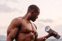 英俊的黑人非裔美国人的肌肉反对日落天空背景的人举的哑铃 图库摄影